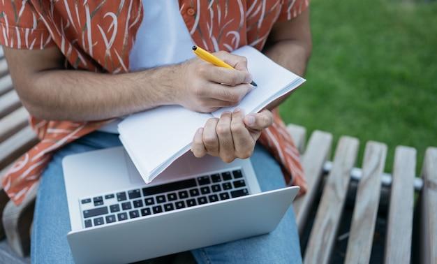 Mãos masculinas fazendo anotações em um caderno, usando um laptop