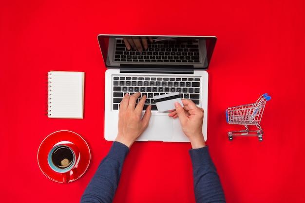 Mãos masculinas fazendo um pagamento com cartão de crédito, conceito de compra online