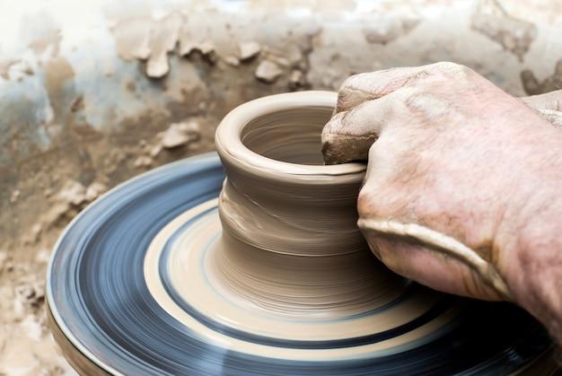 Mãos masculinas fazendo uma caneca de argila em uma roda de oleiro
