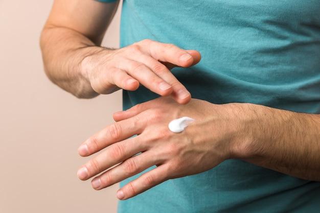 Mãos masculinas hidratando as mãos com creme