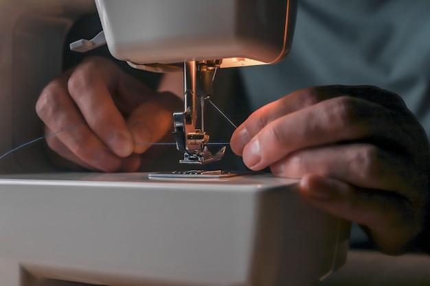 Mãos masculinas inserindo linha através do orifício da agulha na máquina de costura, começando seu trabalho