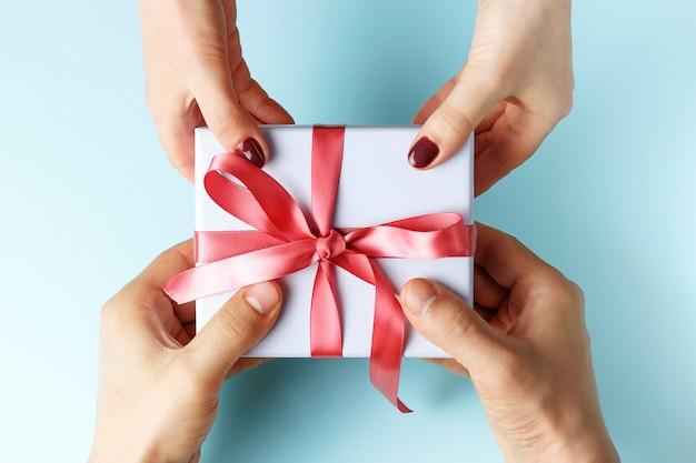 Mãos masculinas passa a caixa de presente para mãos femininas