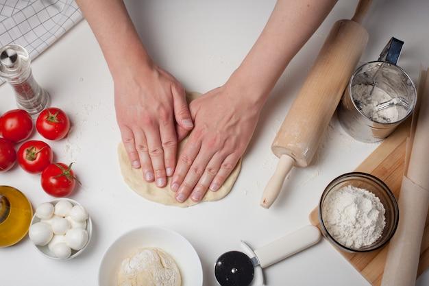 Mãos masculinas que preparam a massa para a pizza.