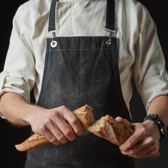 Mãos masculinas quebrando pão fresco, close-up