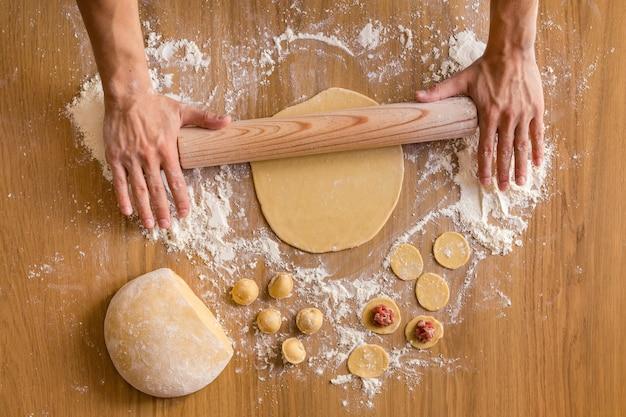 Mãos masculinas rolando massa para preparação de bolinhos de carne na mesa de madeira.