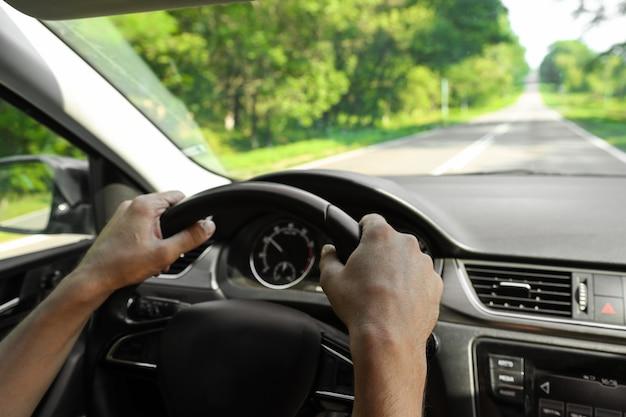 Mãos masculinas seguram o volante de um carro enquanto dirige a vista interna
