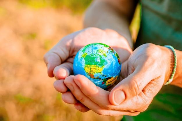 Mãos masculinas seguram um globo ao pôr do sol no parque o conceito de proteção ambiental