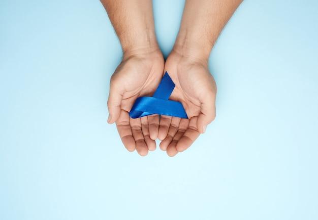 Mãos masculinas seguram uma fita azul escura, conceito de pesquisa oportuna e prevenção de doenças malignas do cólon, síndrome da fadiga crônica, esclerose tuberosa, vista superior