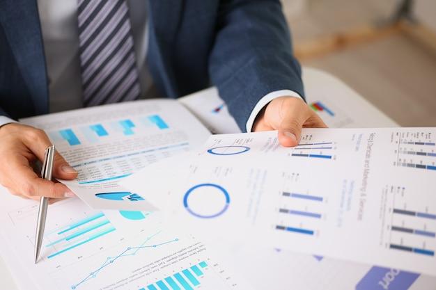 Mãos masculinas segurando documentos com estatísticas financeiras