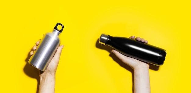 Mãos masculinas segurando duas garrafas térmicas de aço e alumínio para água, preto e prata de cor isolada em amarelo.