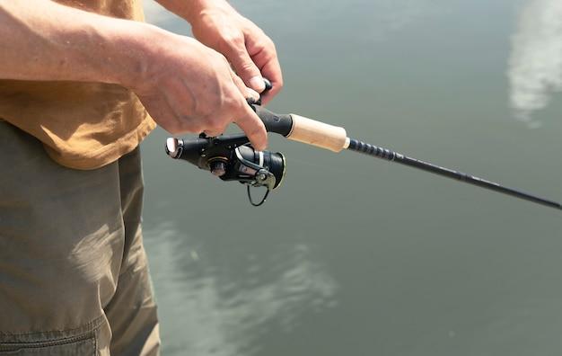 Mãos masculinas segurando e girando a haste do carretel giratório, isca de colher e pesca ao longo do rio, closeup.