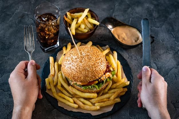Mãos masculinas segurando garfo e faca acima do hambúrguer