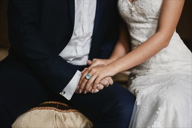 Mãos masculinas segurando lindas mãos femininas com caro anel de ouro com grande diamante.