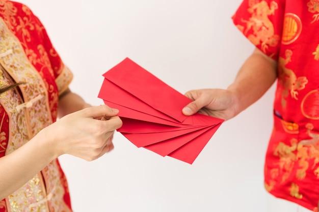 Mãos masculinas segurando muitos envelopes vermelhos em branco com dinheiro de angpao com traje chinês