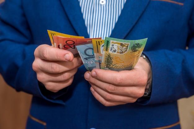 Mãos masculinas segurando notas de dólar australiano, close-up