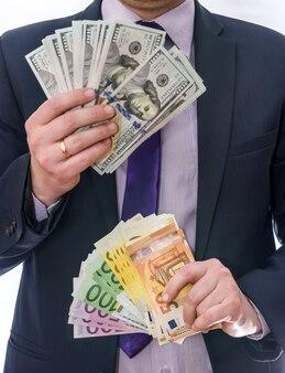 Mãos masculinas segurando notas de dólar e euro em leque