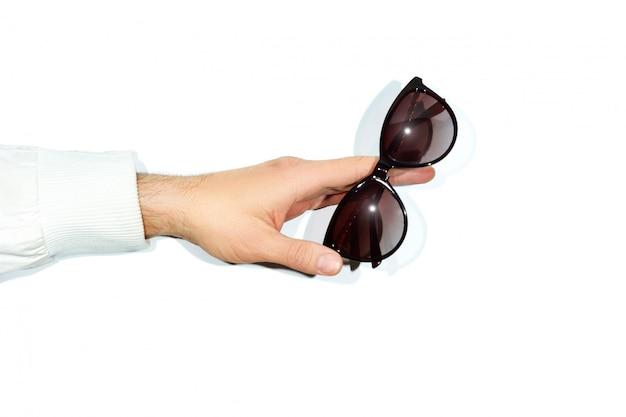 Mãos masculinas segurando óculos de sol branco
