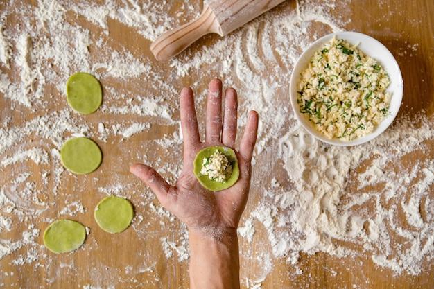 Mãos masculinas segurando um espaço em branco para bolinhos de vegetais. preparação de bolinhos de carne na mesa de madeira.