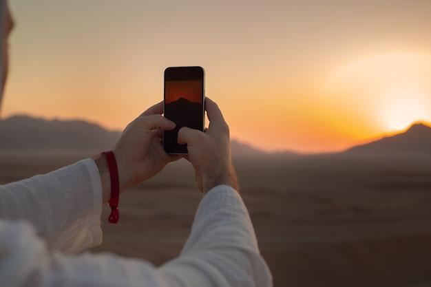 Mãos masculinas segurando um telefone celular com imagem do pôr do sol ou nascer do sol na tela, tirando foto