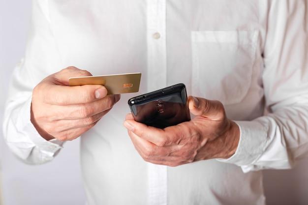 Mãos masculinas segurando um telefone celular e um cartão de plástico, inserindo dados no aplicativo do banco para pagar online. vista frontal, close-up