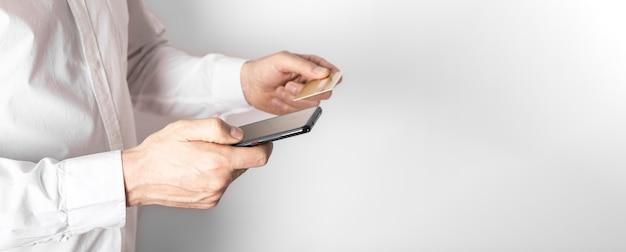 Mãos masculinas segurando um telefone celular e um cartão de plástico, inserindo dados no aplicativo do banco para pagar online.