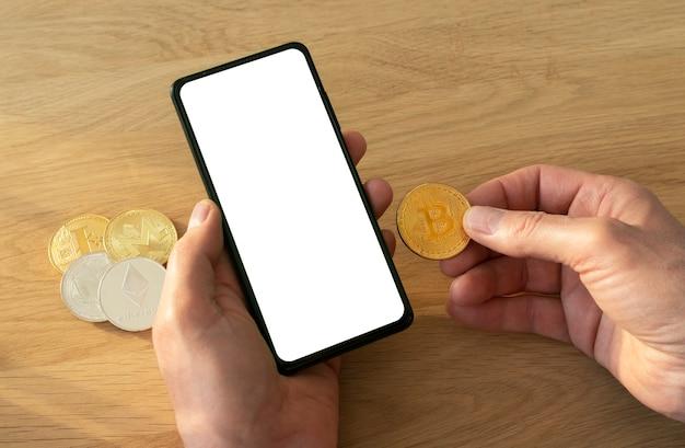 Mãos masculinas segurando um telefone móvel com tela para mock up e moeda bitcoin na mão sobre a mesa de madeira.