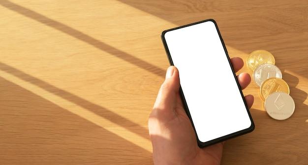 Mãos masculinas segurando um telefone móvel com tela para simulação de aplicativo e moedas de criptografia na mão sobre a mesa de madeira com espaço de cópia.