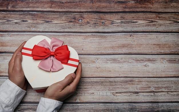Mãos masculinas segurando uma caixa de presente em forma de coração com gravata borboleta. tema dos namorados. conceito lgtbi
