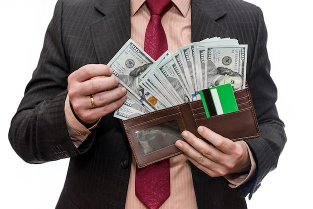 Mãos masculinas segurando uma carteira cheia de notas de dólar, close-up