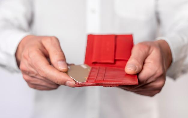 Mãos masculinas segurando uma carteira vermelha com cartões de plástico do banco