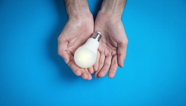 Mãos masculinas segurando uma lâmpada no fundo azul.