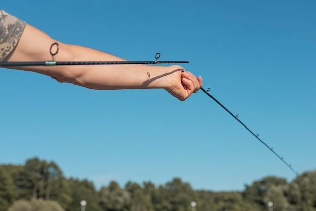 Mãos masculinas segurando uma vara de pescar quebrada e montando-a sobre um céu azul claro no verão