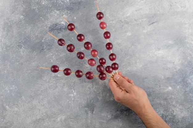 Mãos masculinas segurando uvas vermelhas em fundo de mármore.