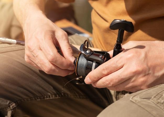 Mãos masculinas segurando vara giratória, isca de colher e fixando ou ajustando antes ou depois de pescar, close-up.