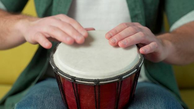Mãos masculinas tocando djembé, bongô no ritmo.