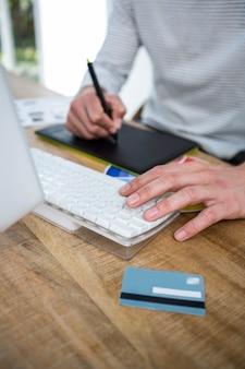 Mãos masculinas, tomando notas e digitando no teclado em um escritório brilhante
