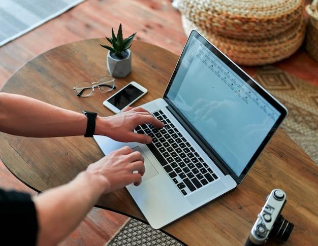 Mãos masculinas trabalham em um laptop moderno em um fundo do interior de uma casa. na mesa de madeira está um telefone, uma planta, uma câmera e óculos.