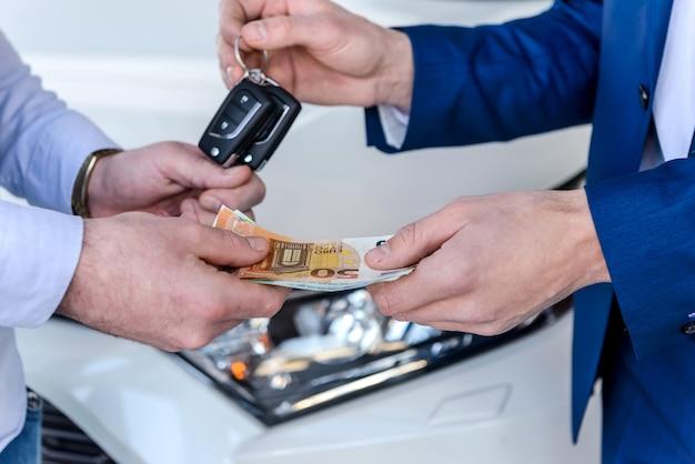 Mãos masculinas trocando por chaves de euro e carro