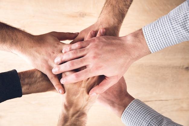 Mãos masculinas uma em cima da outra em uma superfície de madeira