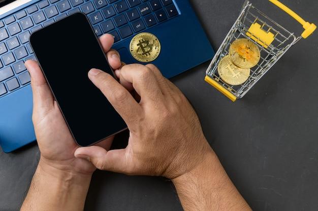 Mãos masculinas usando smartphone para vender ou comprar dinheiro virtual