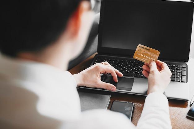 Mãos masculinas usando um cartão de crédito e um laptop para operação online ou internet banking.