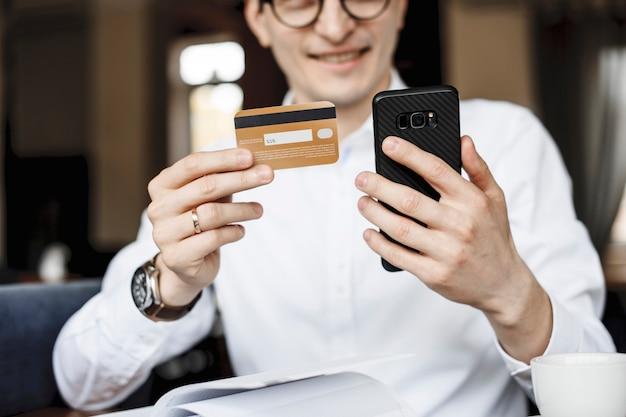 Mãos masculinas usando um smartphone e um cartão de crédito para serviços bancários na internet.