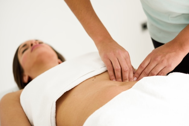 Mãos massageando o abdômen feminino.therapista aplicando pressão sobre a barriga.