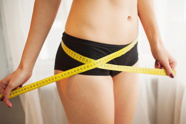 Mãos, medindo a cintura com uma fita. mulher magra e saudável em sua casa