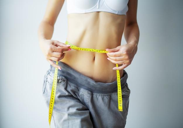 Mãos, medindo a cintura com uma fita. mulher magro e saudável em sua casa