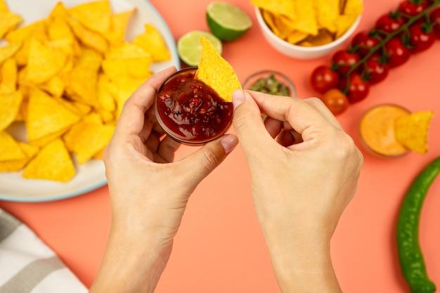 Mãos mergulhando nachos em molho de tomate