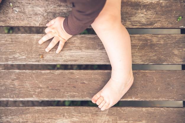 Mãos minúsculas e pés de um bebê, estilo retro.