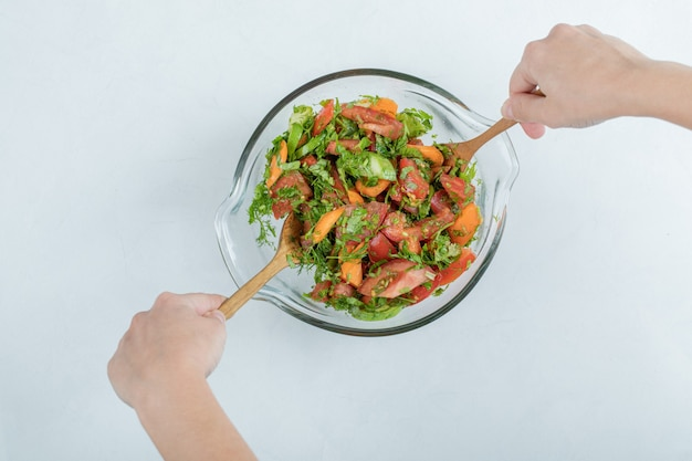 Mãos misturando deliciosa salada de legumes em um prato de vidro.