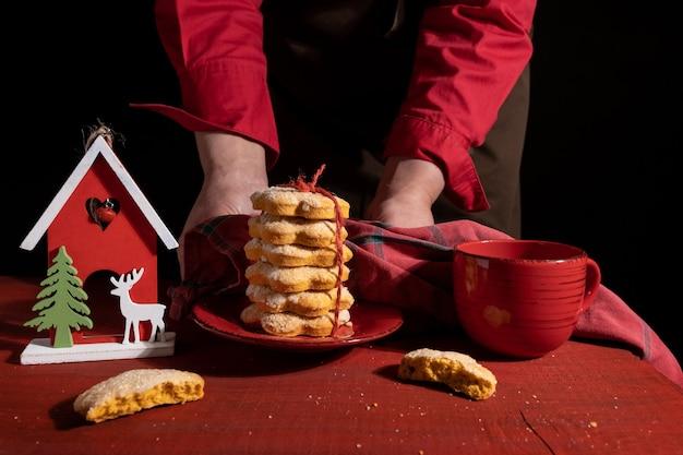 Mãos mostra biscoitos na mesa de madeira vermelha com xícara de café vermelha e brinquedo de ano novo