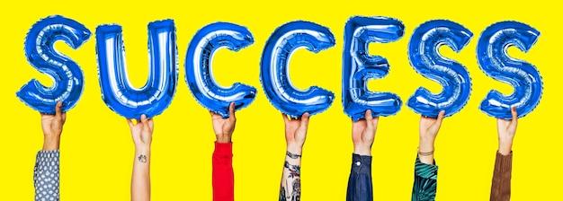 Mãos mostrando a palavra dos balões de sucesso